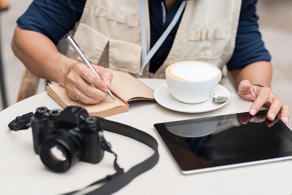periodista anotando tomando un cafe