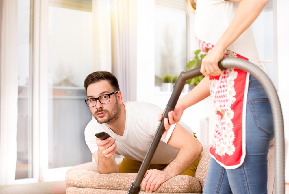hombre viendo deportes mientras la mujer limpia